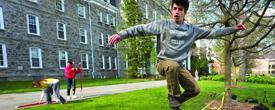 Swat Circus member Jonah Schwartz '15 leaps on a slack line on Parrish Lawn.