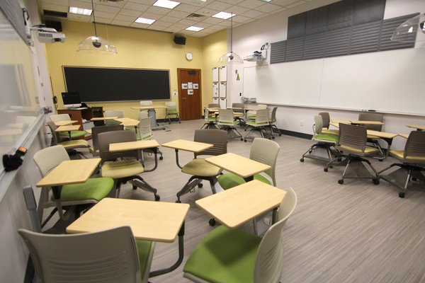 Green tablet arm chairs in Kohlberg room 116