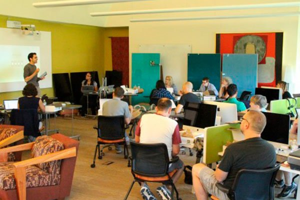 Faculty sitting at computer desks listening to Professor Hauze present about teaching with iPad Pros.