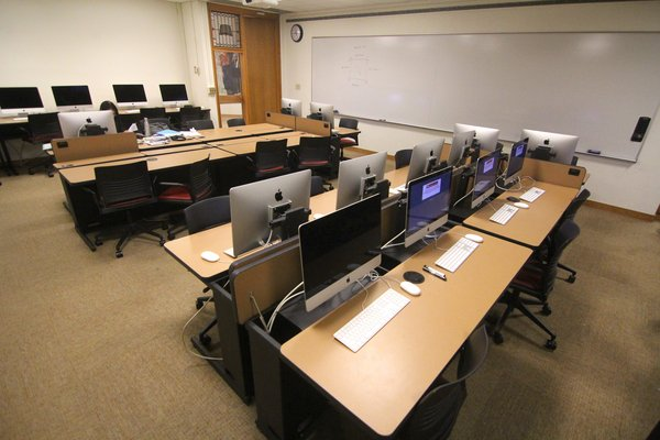 4 rows of desks and computers on retractible arms, 2 large whiteboards are fastened to the walls and a teaching podium is positioned in off to the side of the whiteboards.