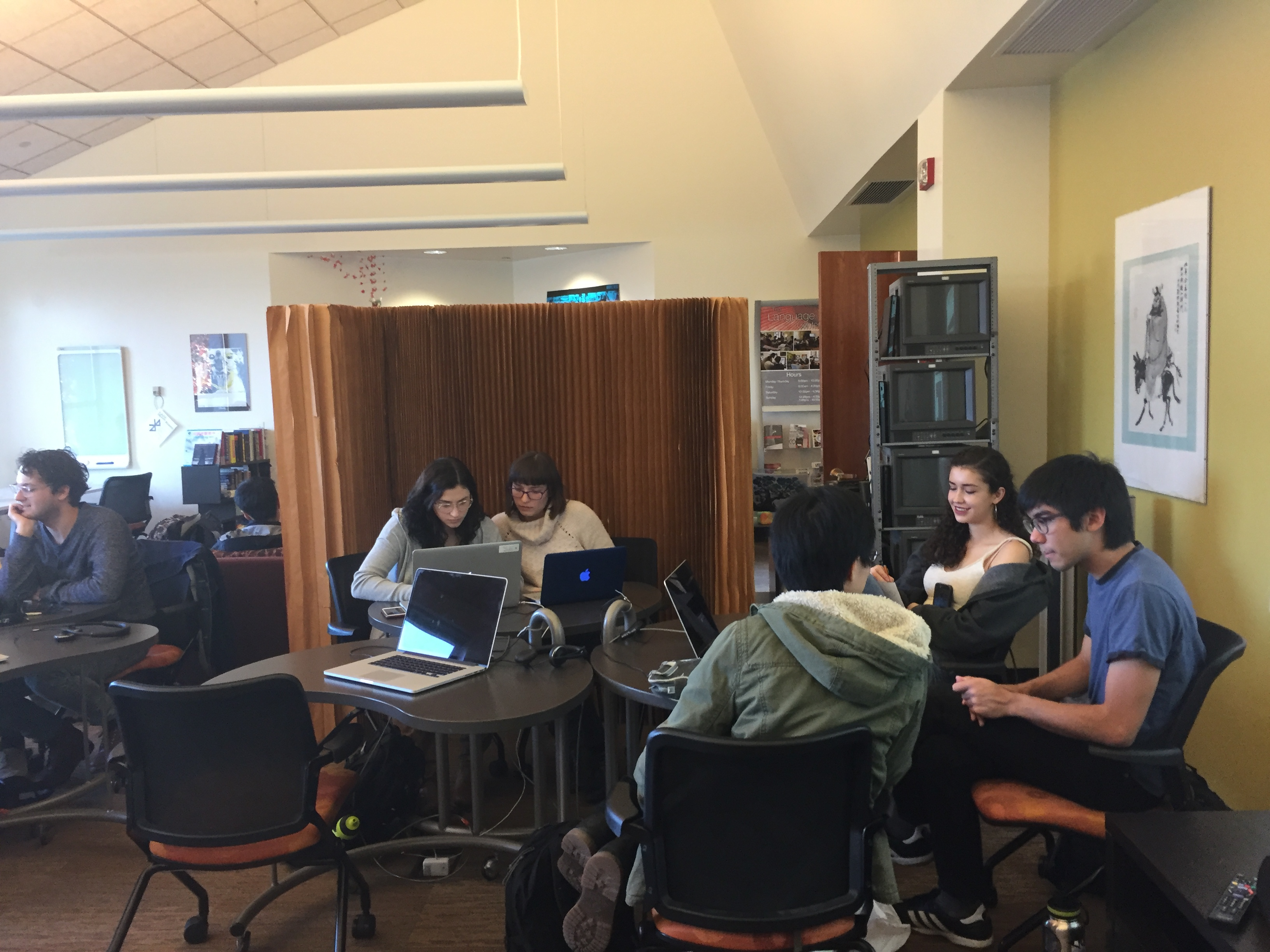 image of five students sitting at two tables (two students at one table, three students at another) in swarthmore's language resource center. the students are smiling and working on collaborative projects.