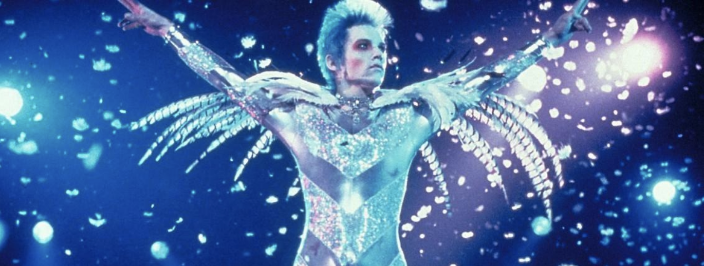 velvet goldmine screenshot; a man in a spangled leotard assumes a heroic pose in front of a sparkling background