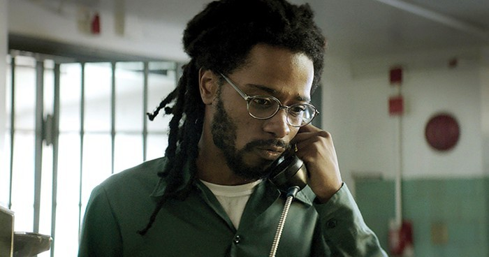 lead character from 'crown heights' stands with a telephone receiver to his ear. he's wearing glasses, a faded jumpsuit, and has loc'd hair