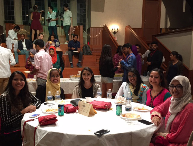 Students smile, sitting around a table during the Eid Banquet
