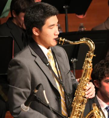 A tenor saxophonist performs with the College Jazz Ensemble.