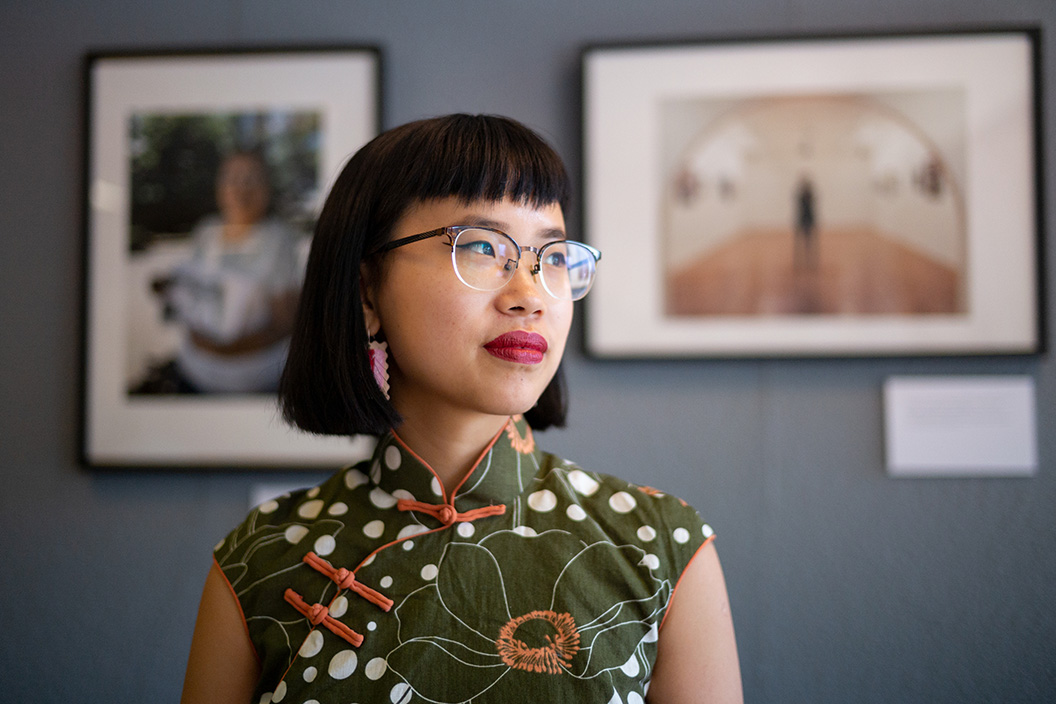 Dorcas Tang '19 in front of framed photographs