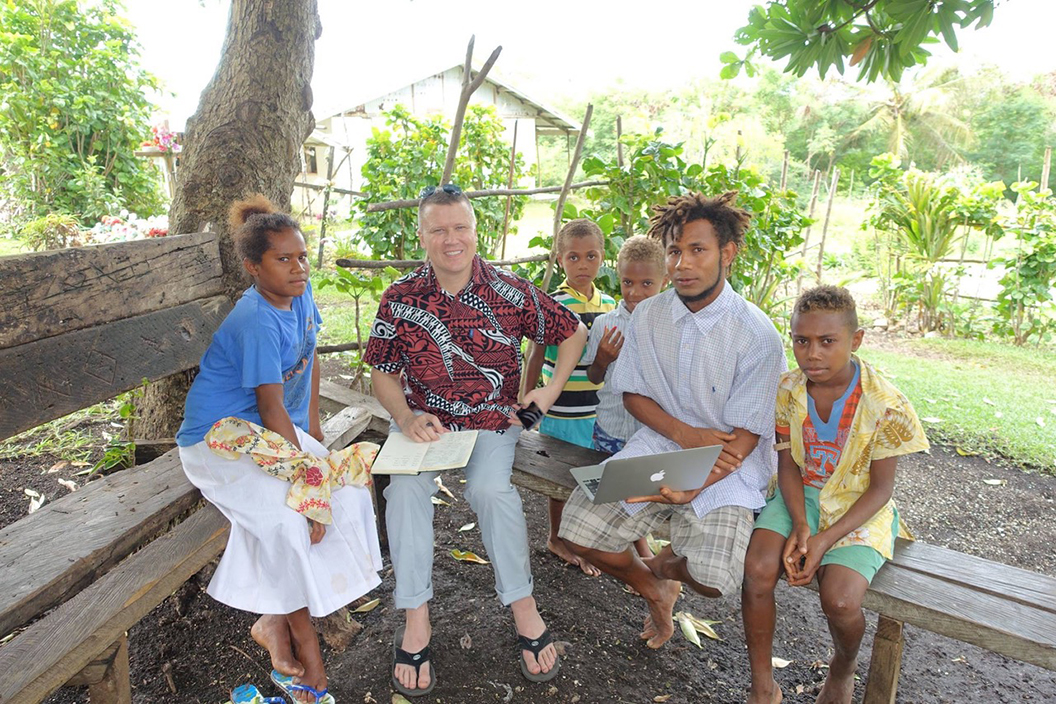 Man sites outside on a bench surrounded by five natives of Vanuatu