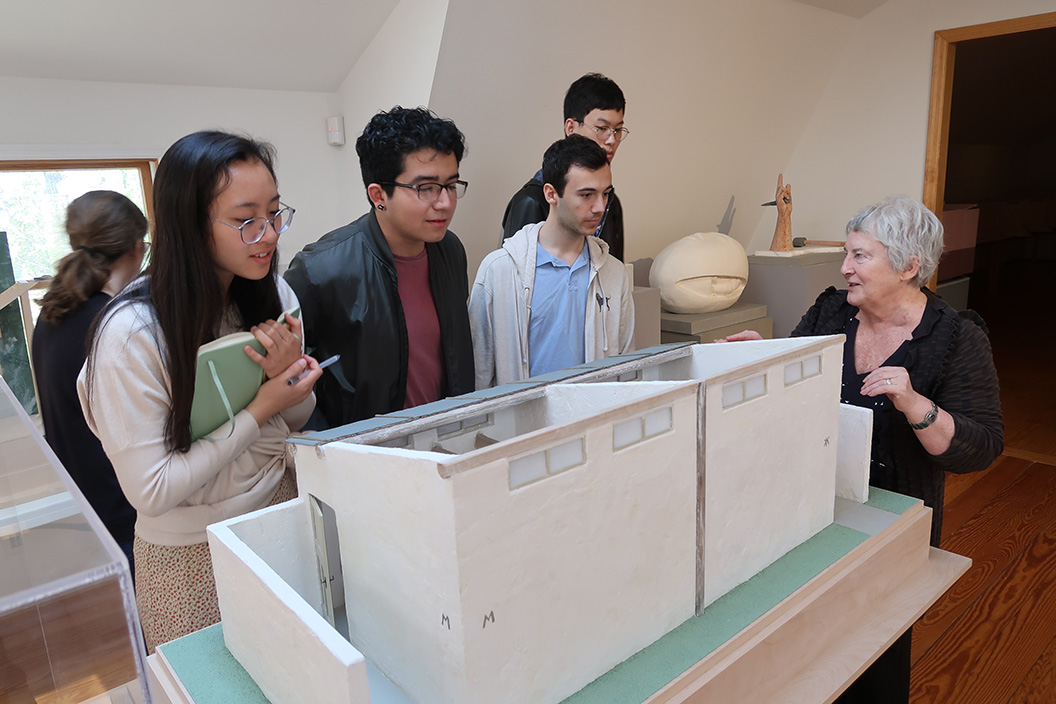 Woman shows students model of building