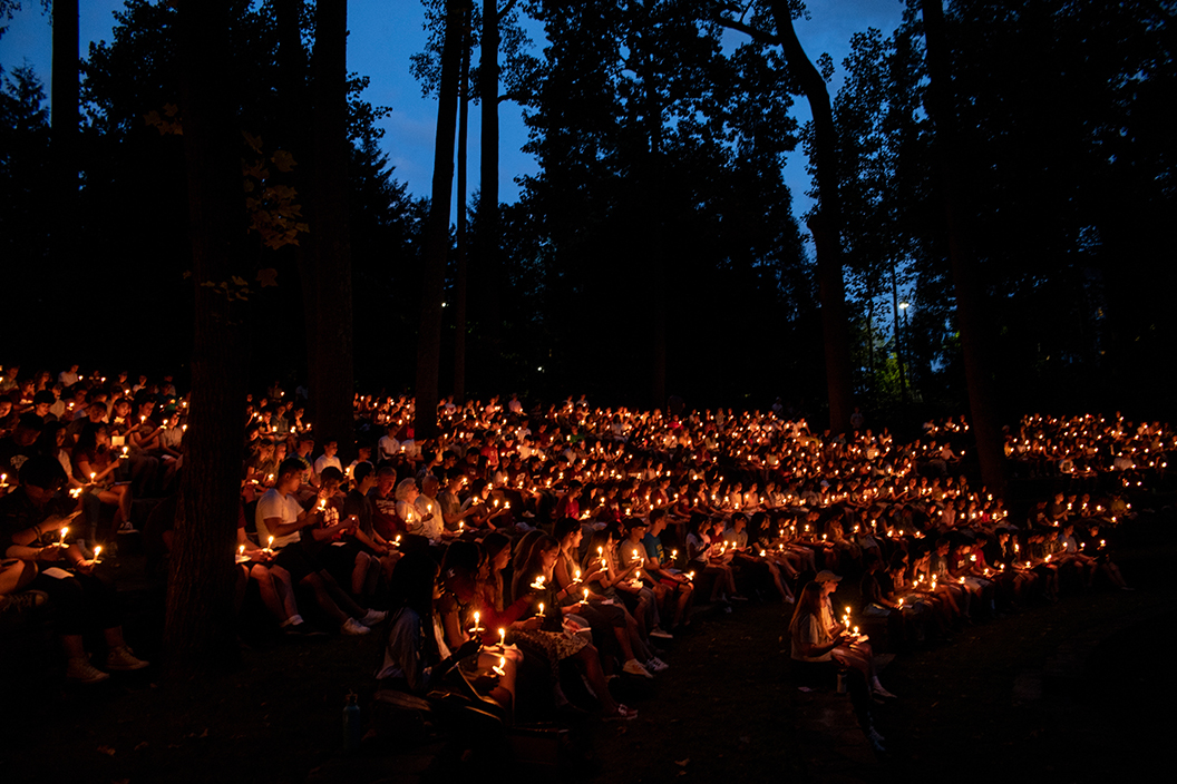Wide shot of students holding candles at first collection