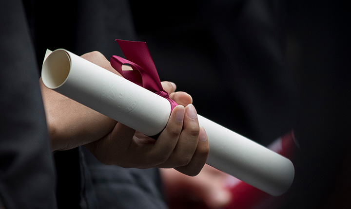 A hand holding a diploma at Commencement 2018