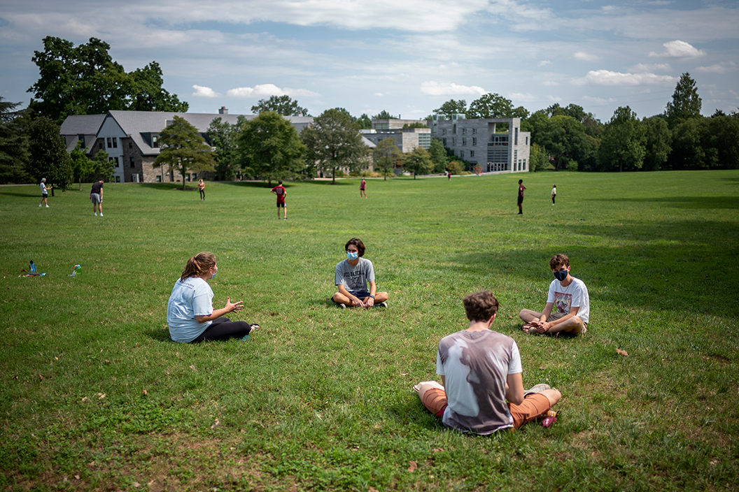 Students sit on grass near Mertz during summer. A few clouds in the sky.