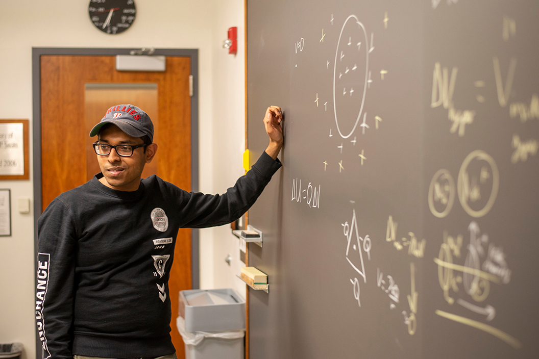 Tarzan Macmood '20 in front of chalkboard with math equations