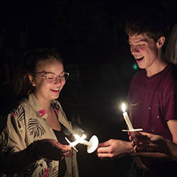two students lighting candles at first collection