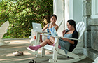 Students sit on rocking chairs on Parrish porch