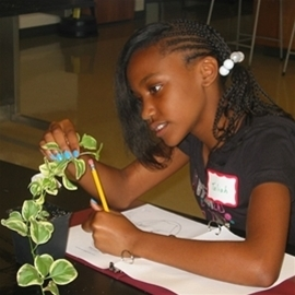 Young student examining a plant and writing observations in a notebook