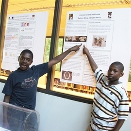 Two enthusiatic students pointing to a concept on their poster.
