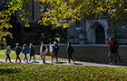 Students walk in front of Clothier Hall on a sunny fall day