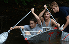 Three students in a handmade watercraft paddle through a creek