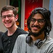 Two male students smiling at Percepticon exhibit