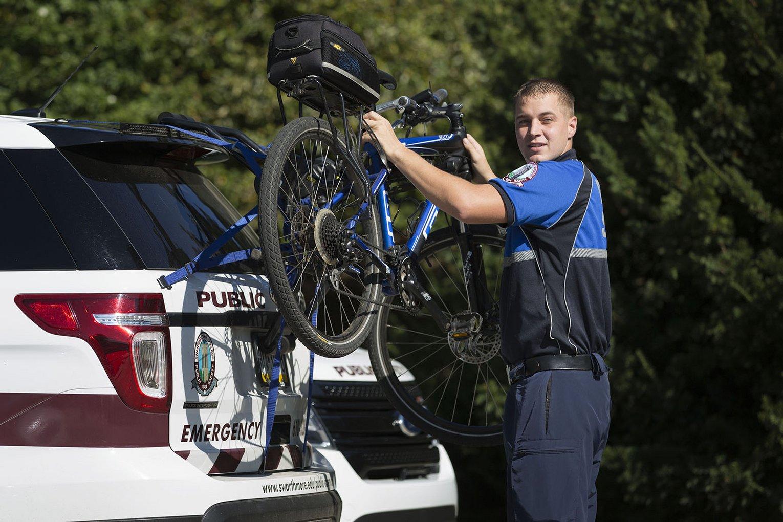 officer placing bike on car rack
