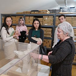 Woman shows group of student art installation under case