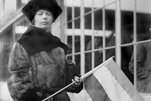 Black and white image of a woman holding a flag as she campaigns for women's suffrage