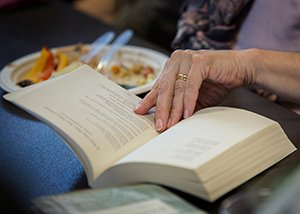 Person's hand turns pages of a book on a table