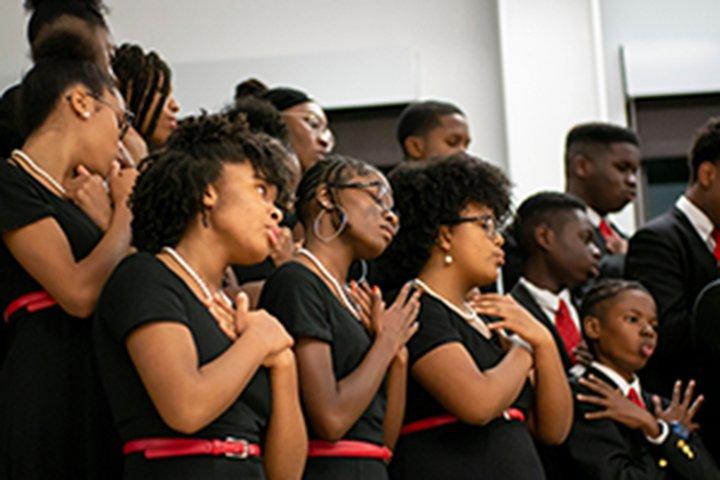 Girls in black dresses sing in chorus
