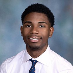 Deante Bryan '20 wearing tie, smiling against blue background