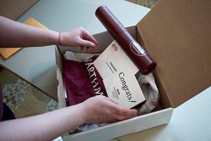 Closeup of hands putting garnet diploma into box