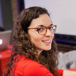 Emma Ferguson in red sweater, wearing glasses