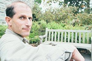 Steve Golub sitting on bench wearing beige shirt looks back at camera