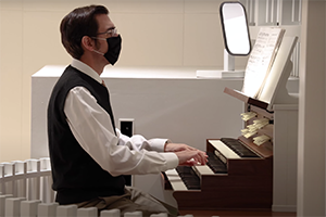 Man in mask sits at pipe organ and plays sheet music