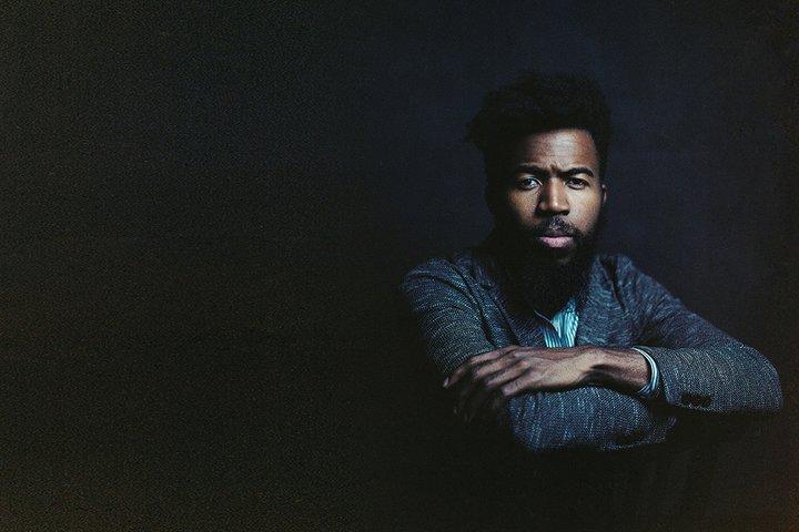 Man in suit sits against dark background
