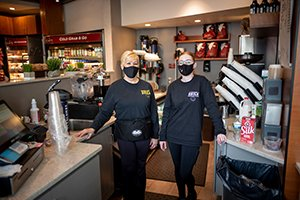 Two masked employees wearing black shirts stands at coffee bar