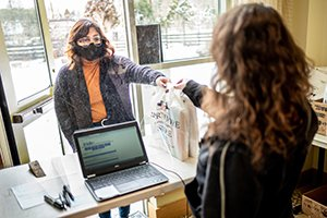 Student in mask handed bag of textbooks from person behind cash register with laptop on desk.