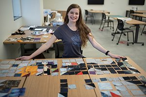 Student sits at table with clothing scraps for making quilt