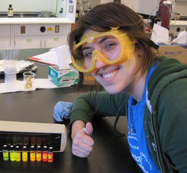 Althea Gaffney, smiling and wearing safety goggles,  gives a thumbs up for chemistry
