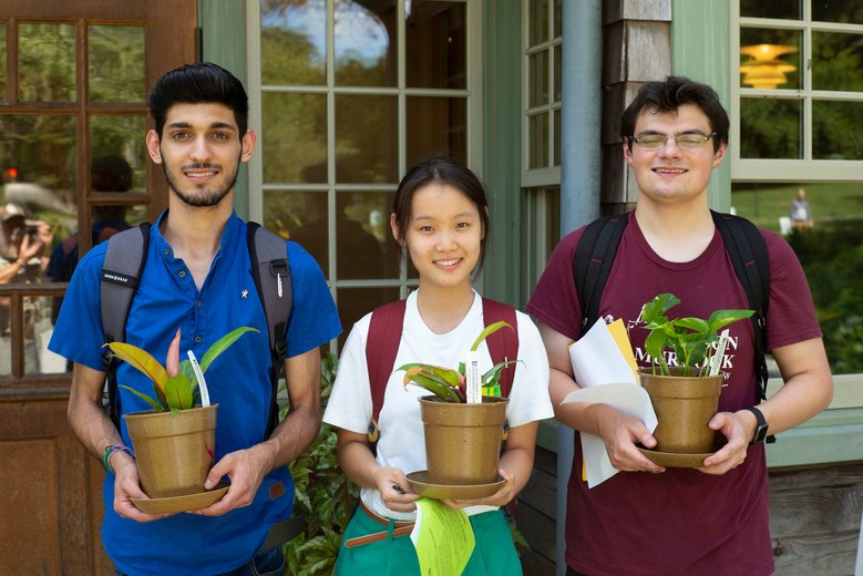 three students holding their free plants during Orientation