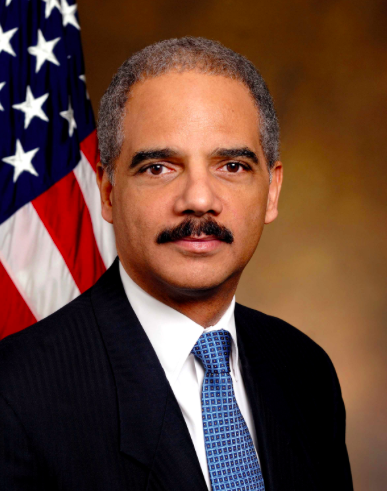 Eric Holder in front of American flag