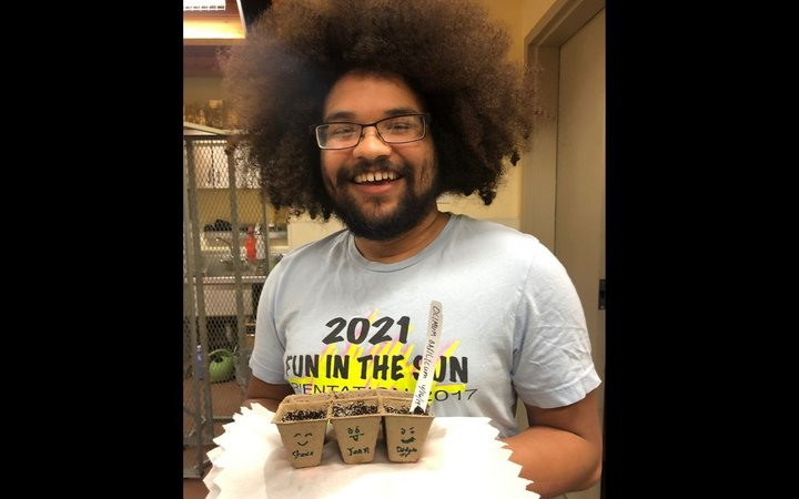 A person with glasses and a beard smiles at the camera while holding seedlings