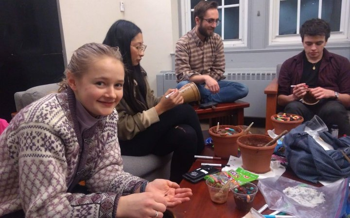 A group of students sit around a table in a dorm lounge covered with craft supplies