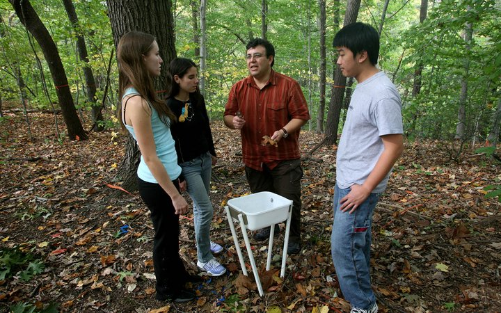 Instructor speaking to students in Crum Woods
