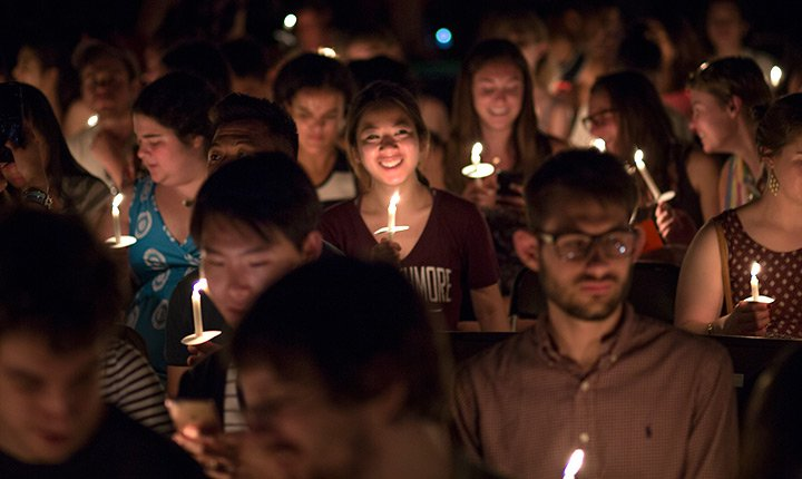 Students stand with their candles