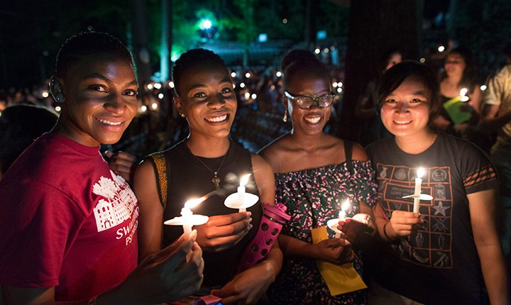 Four students stand with their candles.