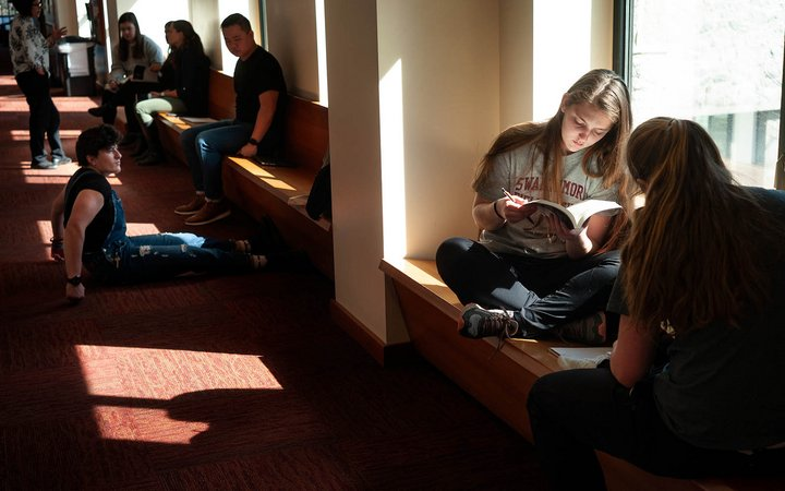 Students reading and lounging in a windowed hallway inside Kohlberg Hall