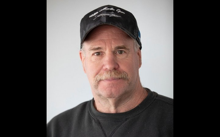Head shot of a man with a white mustache wearing a black baseball cap and black tee shirt.