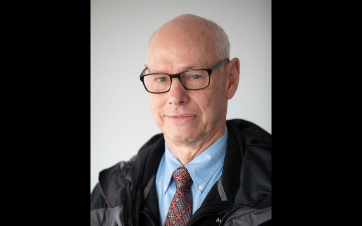 Head shot of bald man with glasses, a red tie, and a blue button down shirt