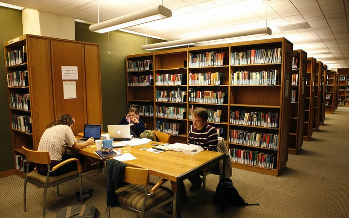 students at a table near book shelves