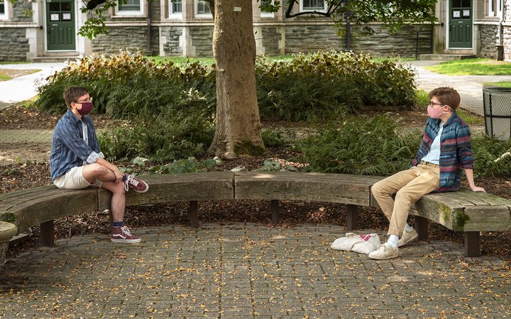 two students talking on bench